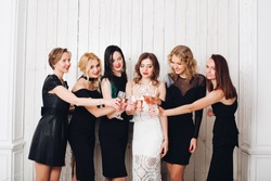 Portrait of beautiful elegant bridesmaids in black dresses toasting glasses of champagne with bride-to-be in lovely white dress.