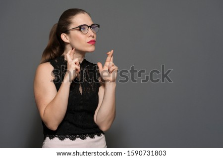 Portrait of beautiful emotional worried caucasian young woman in glasses crossing her fingers and worrying about something on gray background. Concept of betting shops. Advertising space