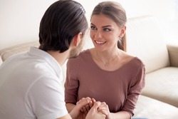 Portrait of beautiful excited woman looking at her boyfriend with affection while he proposing to marry, young man holding ladyâ??s hands declaring his feelings, saying I love you, marriage proposal