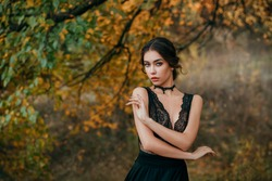 Portrait of beautiful fairy girl in black dark dress standing next to colorful autumn tree bright orange leaves. Art work of romantic elegant medieval woman. Pretty tenderness model looks at camera