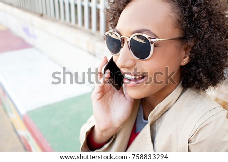 Portrait of beautiful fashion african american teenager girl wearing shades using smart phone on phone call conversation, joyfully smiling outdoors. Black adolescent young woman using technology.