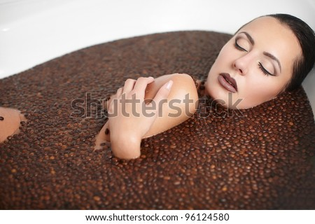 Portrait of beautiful fashion girl in jacuzzi with coffee. Body care. bright makeup