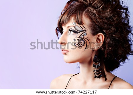 Portrait of beautiful fashionable woman with painted ornament on her face. Studio shot.