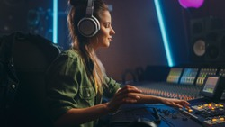 Portrait of Beautiful Female Artist Musician in Music Recording Studio, Uses Headphones.  Successful Female Audio Engineer Uses Mixing Board Create Modern Song.