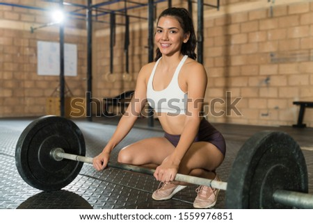 Portrait of beautiful female athlete crouching by barbell while smiling at health club