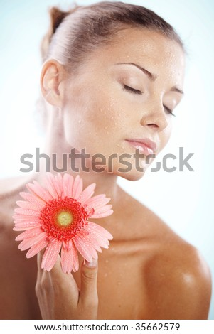 Portrait of beautiful female holding pink daisy with water drops on face