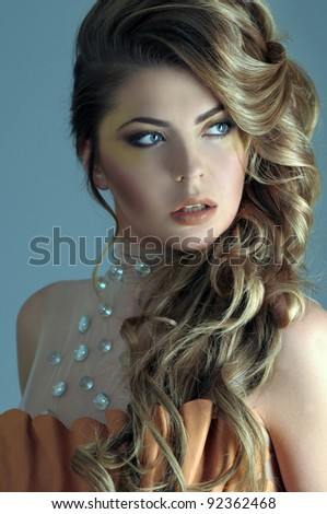Portrait of beautiful female model on light blue background - stock photo