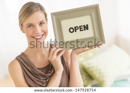"""Portrait of beautiful female owner holding framed """"open"""" sign in bedding store"""