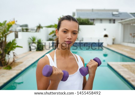 Portrait of beautiful fit mixed-race woman exercising with dumbbells near swimming pool in the backyard. Summer fun at home by the swimming pool #1455458492