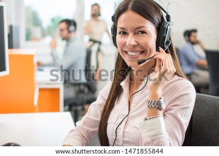 Portrait of beautiful friendly female customer services agent with headset working in call center #1471855844