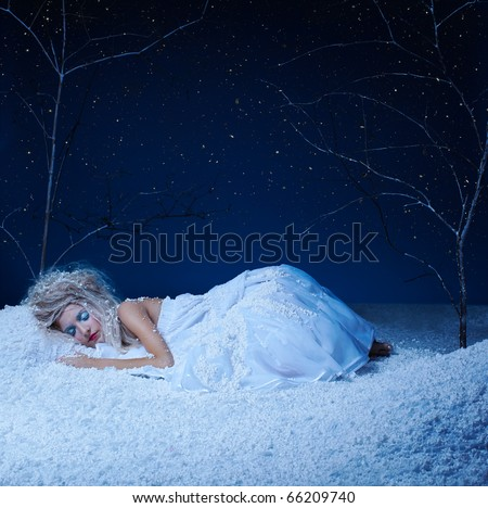 portrait of beautiful frozen fairy nymph girl sleeping on snow
