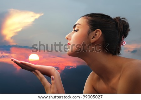 Portrait of beautiful girl holding sun in hands against sunset.