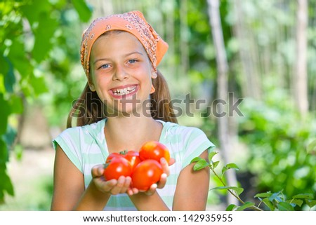 Portrait of beautiful girl holding tomatoes in green garden