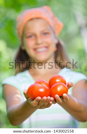 Portrait of beautiful girl holding tomatoes in green garden. Focus on the tomatoes.