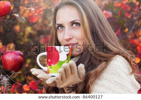 portrait of beautiful girl in autumn leaves. With an cup in hand.