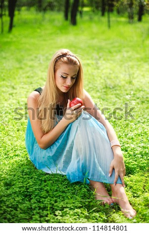 Portrait of beautiful girl in green park with red apple