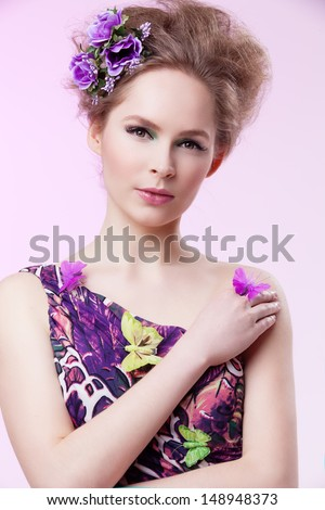 Portrait of beautiful girl in purple dress with butterflies and flowers in her fluffy hair