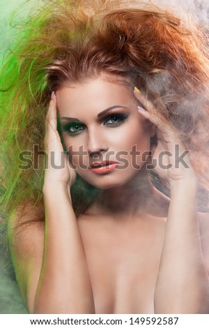 Portrait of beautiful girl in smoke with long red fluffy hair and dramatic makeup