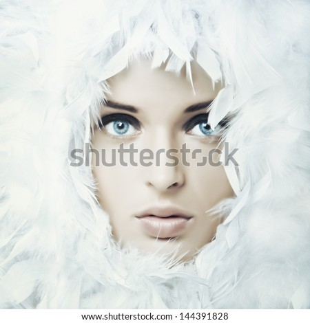 Stock Photo Portrait of beautiful girl in white feathers
