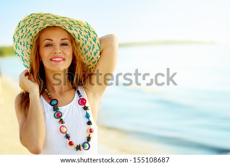 Portrait of beautiful girl on a sunny beach wearing a hat