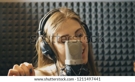 Portrait of beautiful girl singing in sound studio. Young singer emotionally recording new song. Lady sings to microphone. Working of creative musician. Show business concept. Slow motion Close up. #1211497441