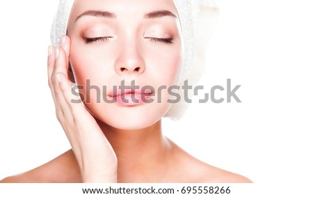 Portrait of beautiful girl touching her face with a towel on  head #695558266