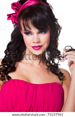 Portrait of beautiful girl with dark long curly hair and vibrant Make-up wearing pink satiny ribbon on white background