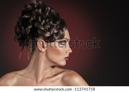 portrait of beautiful girl with elegant coiffure on red background