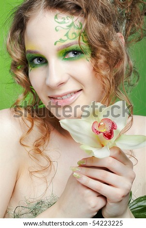 Portrait of beautiful girl with fairy theme bodyart posing with lily