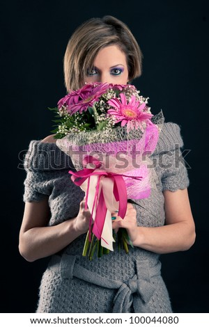 Portrait of beautiful girl with gerbera flowers bouquet and wool dress against black background.