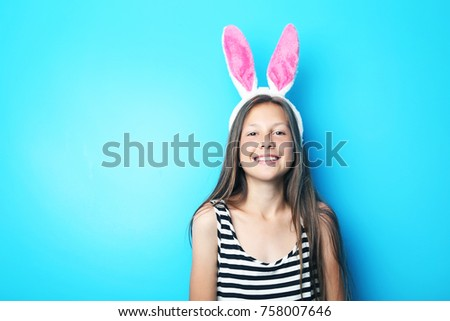 Portrait of beautiful girl with rabbit ears on blue background #758007646
