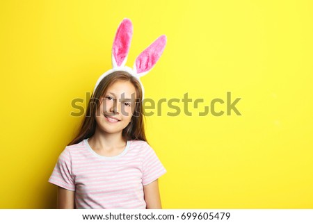 Portrait of beautiful girl with rabbit ears on yellow background #699605479
