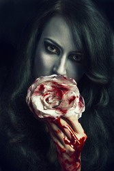portrait of beautiful gothic girl with rose and blood