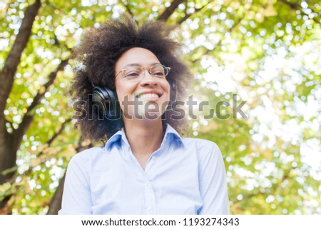 Portrait of Beautiful Happy Afro American Young Woman Listening Music with headphones in nature, attractive mixed race female fun outdoor  #1193274343
