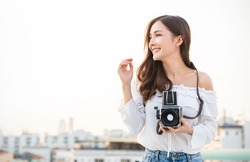 Portrait of beautiful happy asian woman photographer in fashion look taking photo. Pretty cool young woman model with retro film vintage camera curly hair outdoors over rooftop sky with copy space