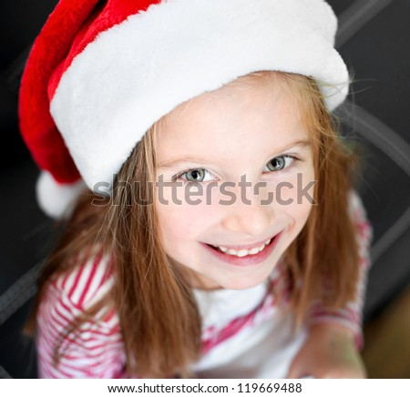 portrait of beautiful happy christmas child in santa hat closeup