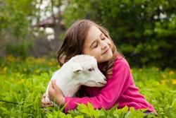 Portrait Of Beautiful Happy Dreamy Little Girl Embracing Little Favorite Goat In Grass In Spring Garden Close Up.
