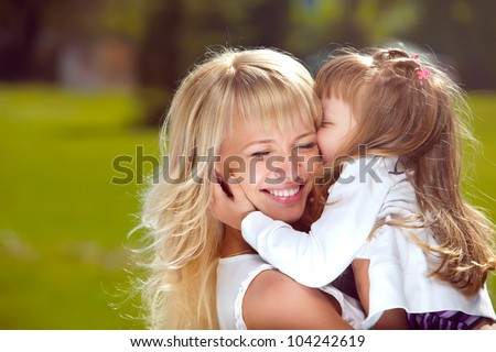 Portrait of beautiful happy mother with her daughter outdoors