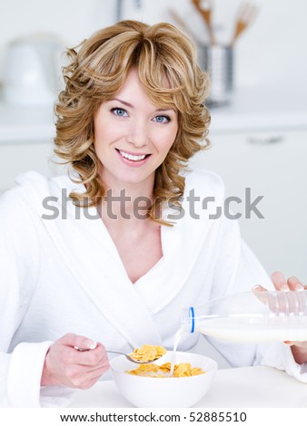 Portrait of beautiful happy smiling woman eating corn flakes in the kitchen