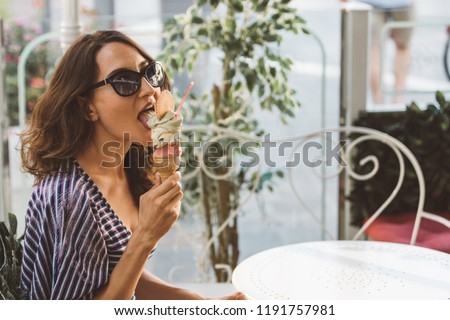 Portrait of beautiful happy woman eating (licking) melting artisanal hand made organic ice-cream in Italian cafe - traveling and healthy Mediterranean food (cuisine) concept - picture with copy space