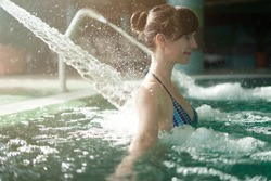 Portrait of beautiful happy woman enjoying indoor adventure pool and hydrotherapy, neck massage jet.