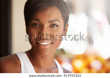 Portrait of beautiful happy young black model with short pixie hairstyle and healthy clean skin looking and smiling at the camera with cheerful expression, showing her white teeth, posing outdoors