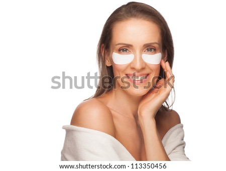 Portrait of beautiful healthy caucasian woman applying gel eye mask . Middle Aged