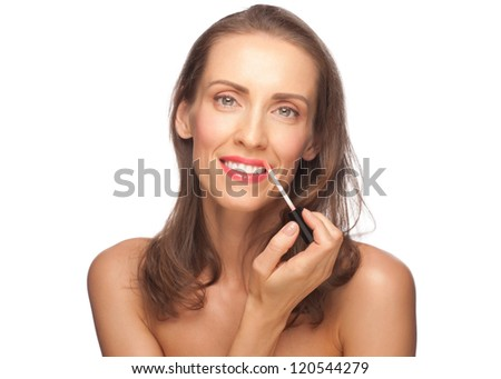 Portrait of beautiful healthy caucasian woman putting on lip gloss. Middle Aged