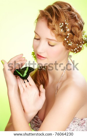 portrait of beautiful healthy redhead teen girl with flowers in her hair holding butterfly on hand