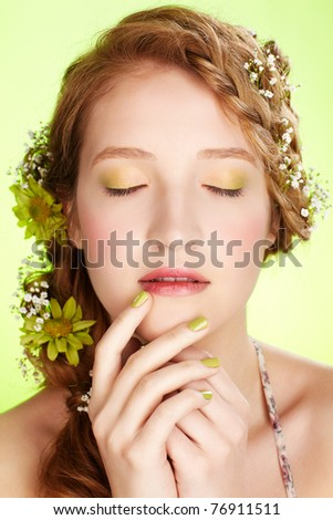 portrait of beautiful healthy redhead teen girl with flowers in her hair on green
