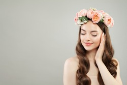 Portrait of beautiful healthy woman with clear skin, curly hair and rose flowers wreath