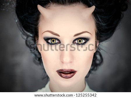 Portrait of beautiful horned woman with bright makeup, conceptual photo