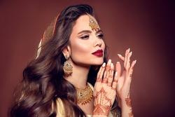 Portrait of beautiful indian girl in sari. Young hindu woman model with kundan golden jewelry set. Traditional Indian costume lehenga choli. Mehendi Henna painting on woman's hands.