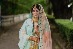 Portrait of beautiful Indian girl wearing wedding lehenga. Young Hindu woman model with tattoo mehndi and kundan jewelry . Traditional Indian wedding costume lehenga choli.